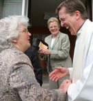 a priest shaking hands with a parishioner